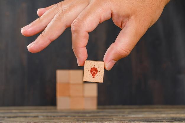 Conceito de inovação na vista lateral da mesa de madeira. mão segurando o cubo de madeira com ícone.