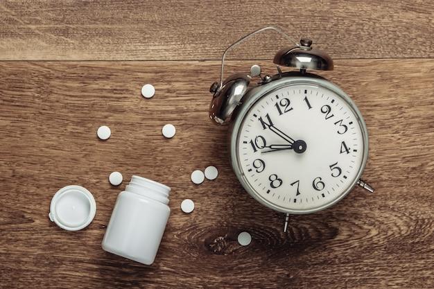 Conceito de insônia. relógio despertador e um frasco de comprimidos no chão. vista do topo