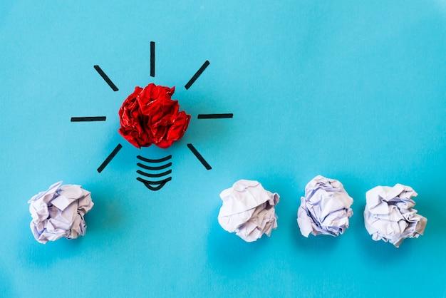 Conceito de inspiração e grande ideia. lâmpada com papel colorido amassado.