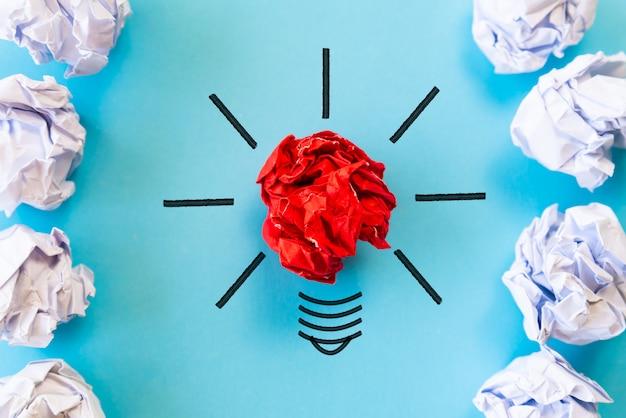 Conceito de inspiração e ideia. lâmpada com papel colorido amassado no fundo azul