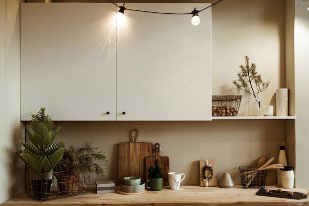 Conceito de interior de cozinha moderna em casa. ramos de abeto, tábuas de cortar madeira, pratos, cesto de nozes, utensílios.