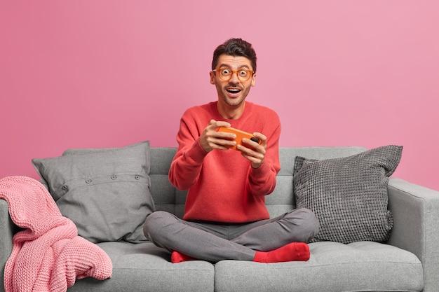 Conceito de internet e jogos de tecnologia. homem caucasiano empolgado joga jogo no smartphone e olha para a câmera de forma surpreendente