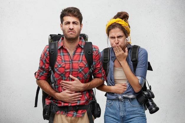 Conceito de intoxicação alimentar, náusea e doença. retrato de turistas jovem, homem e mulher, sentindo dor de estômago, sofrendo de diarréia depois de comerem comida exótica durante a viagem no país asiático