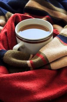 Conceito de inverno feliz. xícara de café na camisola vermelha. sobre a luz