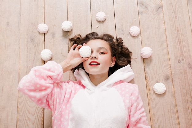 Conceito de inverno, natal, férias, doces, aniversário, celebração e crianças - pijama de menina bonitinha com doces sentado no chão, conceito de infância feliz. presentes de menina, cachorro macio, bolhas de sabão.