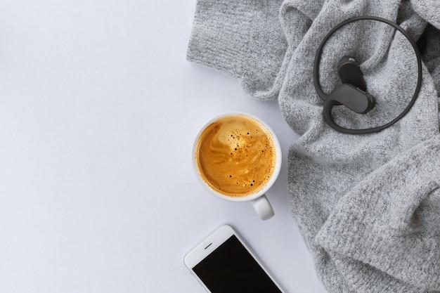 Conceito de inverno. xícara de café com suéter no fundo da mesa branca. vista do topo