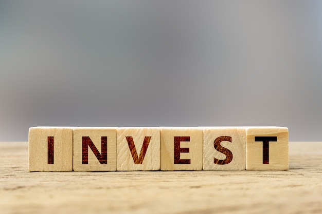Conceito de investimento. bloco de madeira com texto na tabela de madeira.