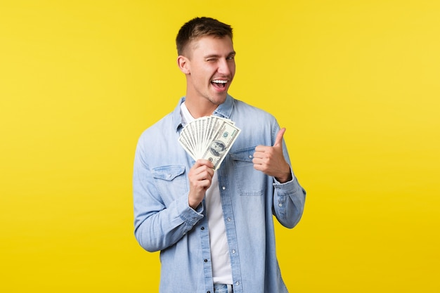 Conceito de investimento, compras e finanças. homem loiro bonito atrevido mostrando o polegar para cima e piscando, sorrindo enquanto encoraja a tentativa de loteria ou cassino, fundo amarelo em pé.