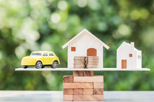 Conceito de investimento imobiliário de negócio: casa de madeira, carro com pilha de moedas de dinheiro
