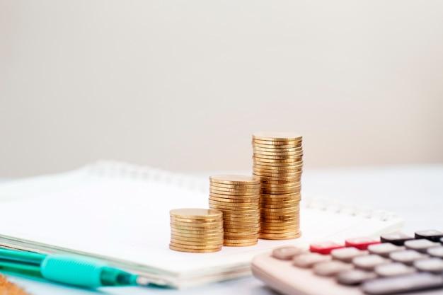 Conceito de investimento imobiliário, moedas de dinheiro que crescem na mesa.