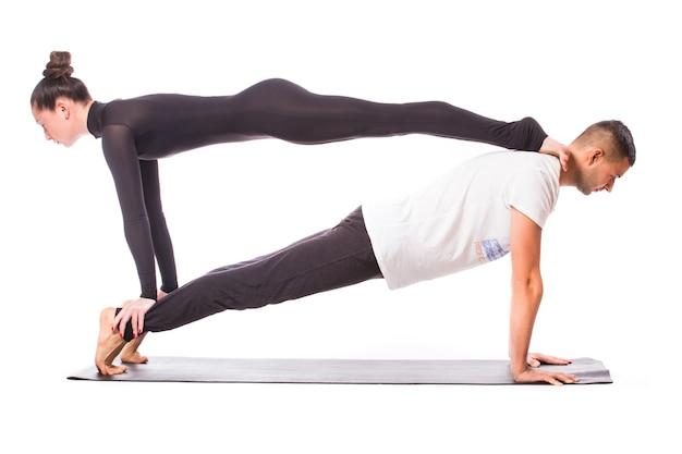 Conceito de ioga de casal. jovem casal saudável em posição de ioga em fundo branco