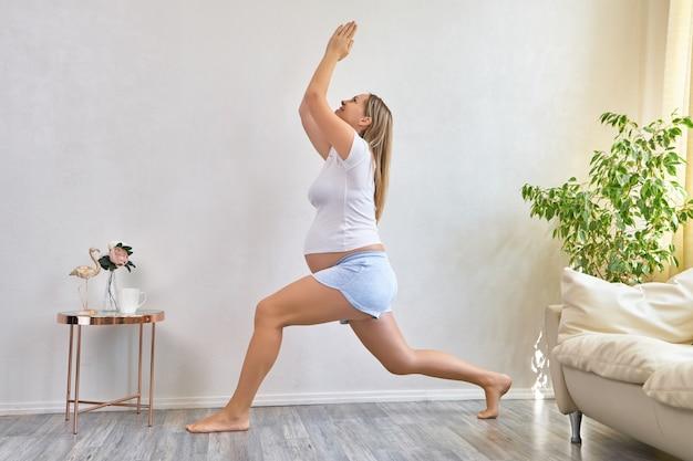 Conceito de ioga e fitness de gravidez saudável. mulher jovem grávida ioga malhando no interior da acolhedora sala de estar.