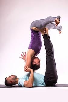 Conceito de ioga. jovem casal saudável em posição de ioga em fundo branco