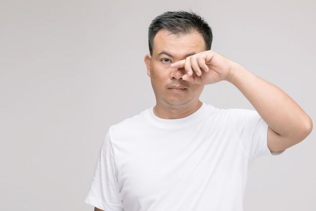 Conceito de irritação nos olhos: retrato de homem asiático em postura de olhos cansados, irritação ou problema nos olhos.