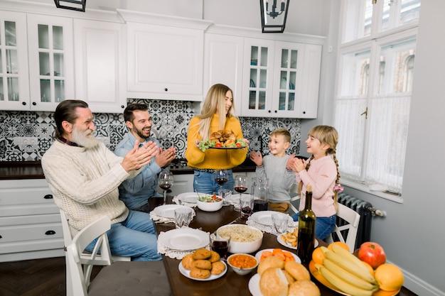 Conceito de jantar de ação de graças: mulher segurando o prato com peru assado e enfeite para jantar em família em casa
