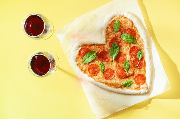 Conceito de jantar romântico a dois com vinho tinto e pizza em forma de coração. jantar para o dia dos namorados
