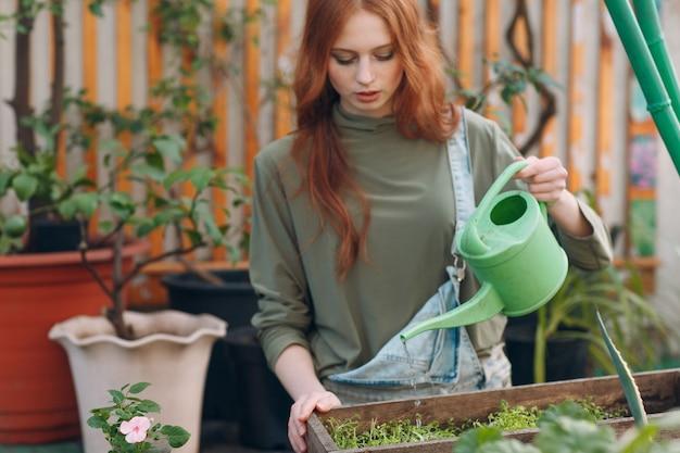 Conceito de jardinagem em casa. jovem mulher planta floral em estufa.