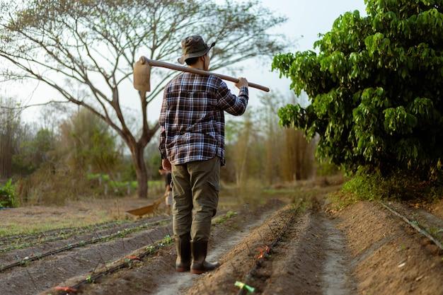 Conceito de jardinagem: um agricultor carregando uma enxada no ombro e deixando um jardim depois de terminar de cultivar.