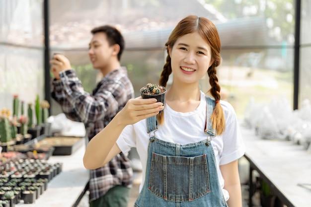 Conceito de jardineiro feminino uma jovem adolescente com duas tranças, mostrando um pequeno pote preto de cactos na estufa com outro adolescente na estufa.