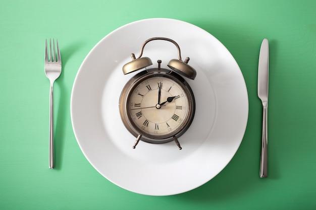 Conceito de jejum intermitente, dieta cetogênica, perda de peso. despertador em um prato