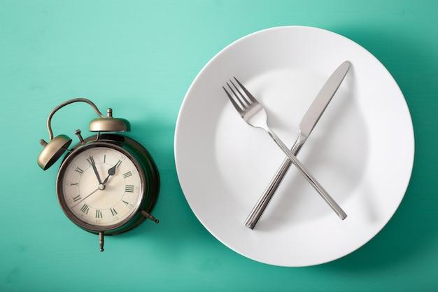 Conceito de jejum intermitente, dieta cetogênica, perda de peso. garfo e faca cruzados em um prato e despertador