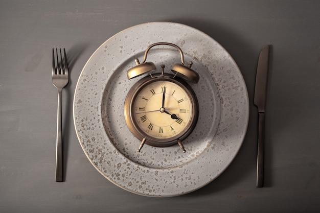 Conceito de jejum intermitente, dieta cetogênica, perda de peso. garfo e faca, despertador no prato