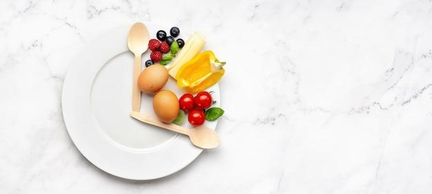 Conceito de jejum intermitente representado com um prato e produtos na mesa branca. estilo de vida saudável. conceito de perda de gordura. vista superior e espaço de cópia