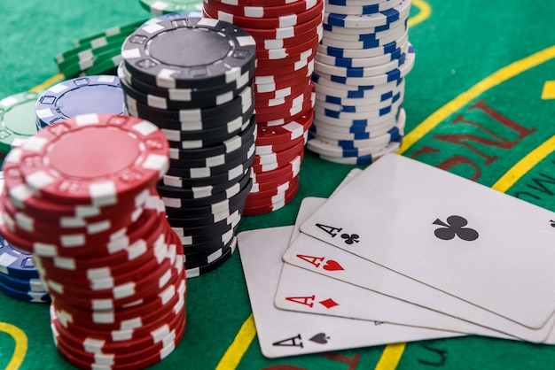 Conceito de jogo. combinação de quatro ases com fichas de pôquer na mesa verde
