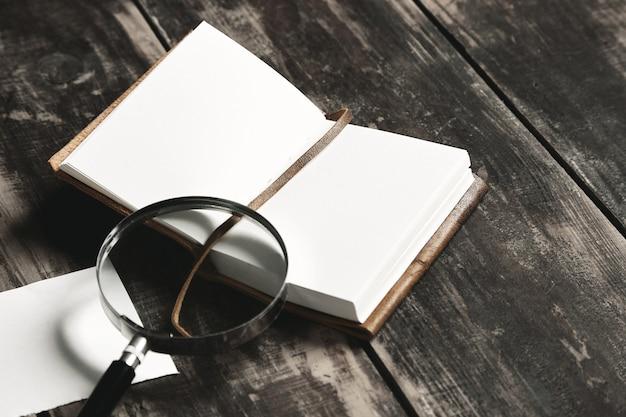 Conceito de jogo de detetive misterioso. caderno aberto com capa de couro, folha de papel branco e uma grande lupa vintage isolada na mesa de madeira preta envelhecida, closeup, vista lateral