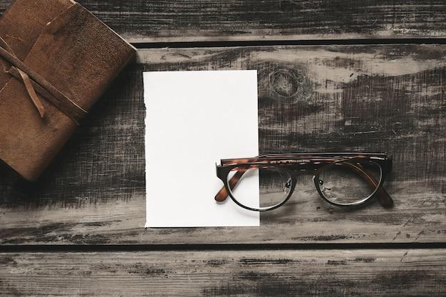 Conceito de jogo de detetive misterioso. caderno fechado em capa de couro, folha de papel branco e óculos de aço inoxidável isolados em mesa de madeira preta envelhecida