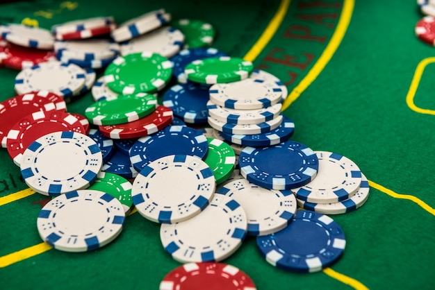 Conceito de jogo e entretenimento com muitas fichas de cassino diferentes na superfície da mesa de jogo