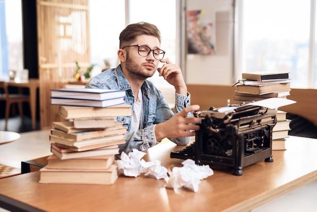 Conceito de jovem freelancer trabalhando na máquina de escrever.