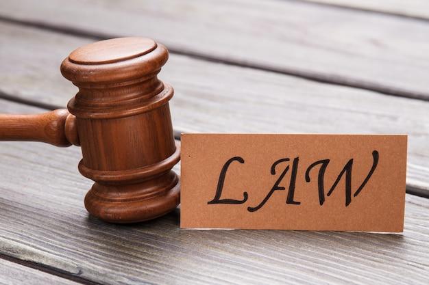 Conceito de julgamento e direito. martelo de madeira do close-up e palavra da lei na mesa.