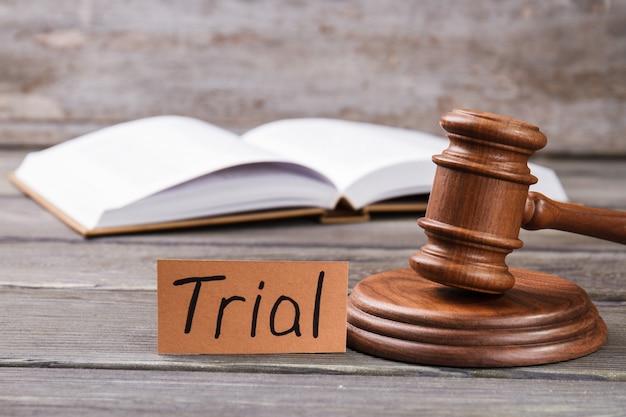 Conceito de julgamento em tribunal. martelo de madeira e livro aberto sobre a mesa.