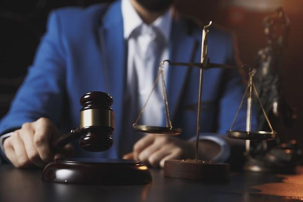 Conceito de justiça e direito. advogado masculino no escritório com balança de latão na mesa de madeira, refletido