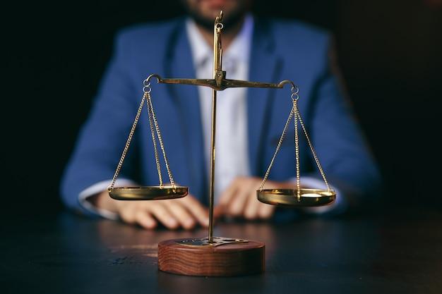 Conceito de justiça e direito. advogado masculino no escritório com balança de latão na mesa de madeira, vista refletida