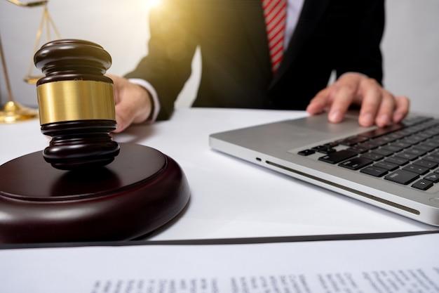 Conceito de justiça e direito. juiz masculino em um tribunal com o martelo, trabalhando com, teclado de encaixe de computador tablet digital, óculos, luz solar de cores quentes na mesa de madeira.