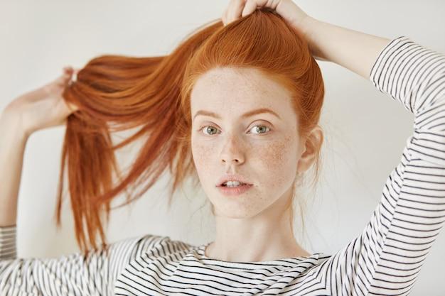 Conceito de juventude, tenra idade e estilo de vida. mulher jovem elegante com sardas amarrando seu lindo cabelo ruivo em um rabo de cavalo