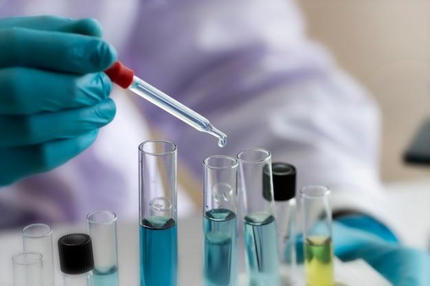 Conceito de laboratório; cientista usa conta-gotas para transferir reagente químico para o tubo de ensaio. ele observa a reação química em laboratório.