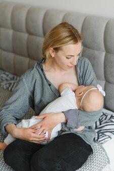 Conceito de lactação. jovem mãe amamentando seu bebê recém-nascido em casa, close-up