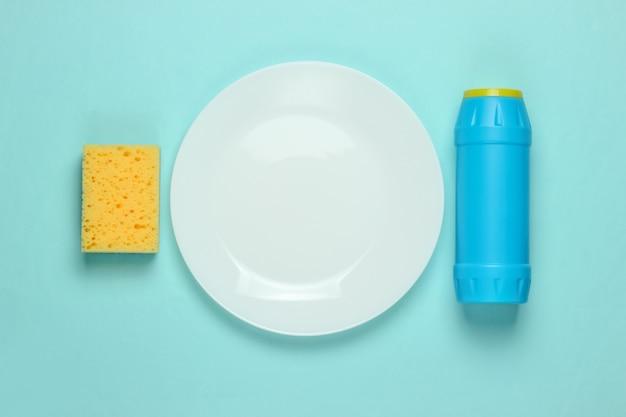 Conceito de lavagem de pratos. prato com uma esponja, frasco de detergente em um fundo azul pastel. vista do topo