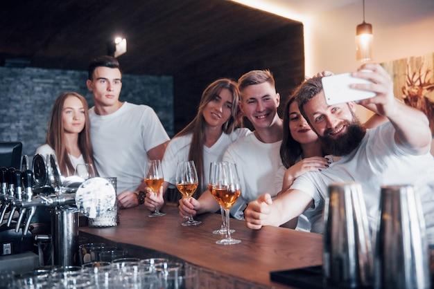 Conceito de lazer e comunicação. grupo de amigos felizes e sorridentes, desfrutando de bebidas e conversando no bar ou pub e tirando uma foto de selfie.