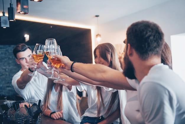 Conceito de lazer e comunicação. grupo de amigos sorrindo felizes desfrutando de bebidas e conversando no bar ou pub