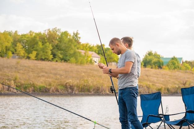 Conceito de lazer e pessoas. amigos felizes com varas de pesca no cais à beira do lago.