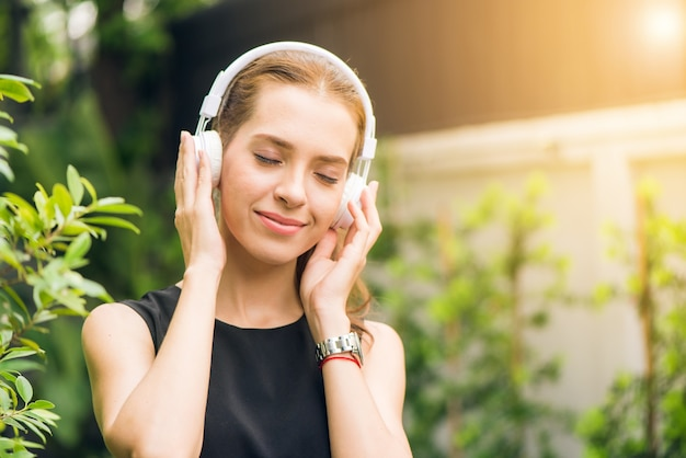 Conceito de lazer e tecnologia de pessoas - jovem atraente que escuta música no leitor de música ao ar livre. menina do hipster que gosta das músicas em seus fones de ouvido no parque da manhã. lens flare.