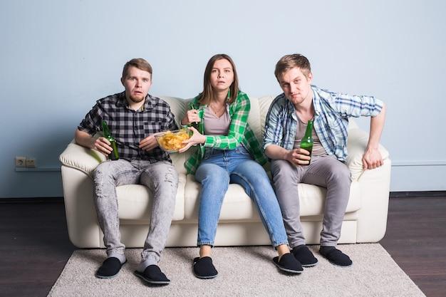 Conceito de lazer, esporte e entretenimento - amigos felizes ou fãs de futebol assistindo a um jogo de futebol na tv e comemorando a vitória em casa.