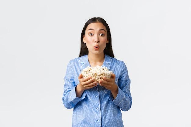 Conceito de lazer, festa do pijama e festa do pijama em casa. excitada e intrigada menina asiática de pijama assistindo com diversão e interesse na tela da tv, assistindo filme e comendo pipoca, fundo branco.