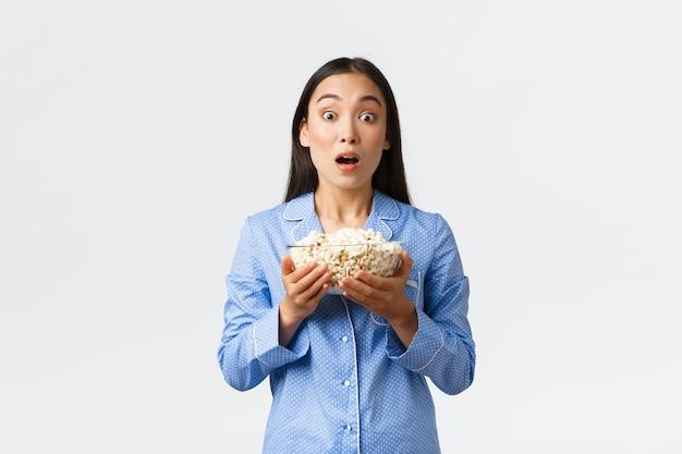 Conceito de lazer, festa do pijama e festa do pijama em casa. linda garota asiática espantada de pijama, segurando a tigela de pipoca e o queixo caído, ofegando enquanto olha para a tv assistindo uma cena de filme interessante, fundo branco.