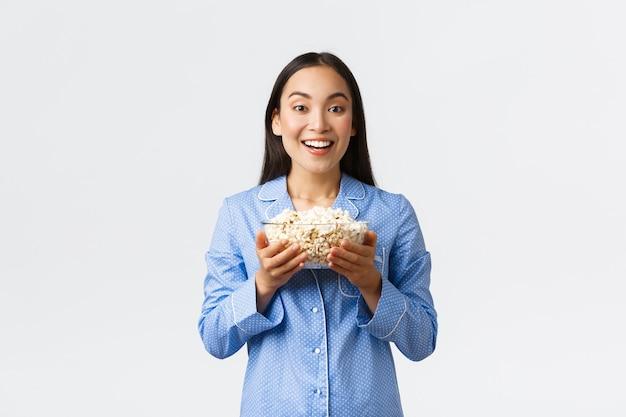 Conceito de lazer, festa do pijama e festa do pijama em casa. sorrindo satisfeita menina asiática, aproveitando os fins de semana na cama com pipoca, comendo e assistindo filmes de pijama, fundo branco de pé.