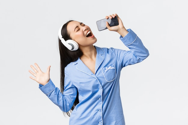 Conceito de lazer, fins de semana e estilo de vida em casa. menina asiática animada e despreocupada de pijama, jogando aplicativo de karaokê no smartphone, cantando no celular usando fones de ouvido, parede branca